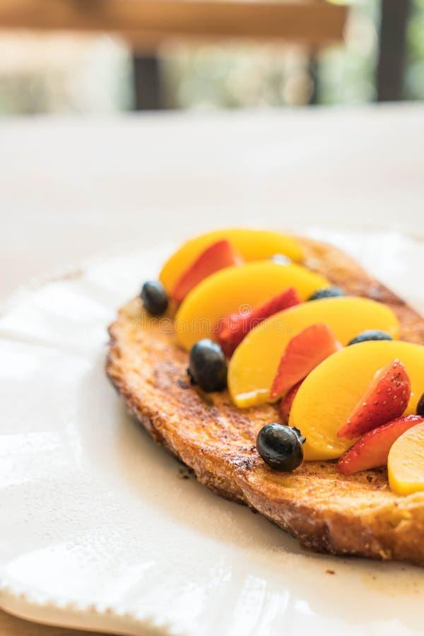 pane tostato francese con la pesca, la fragola ed i mirtilli fotografie stock