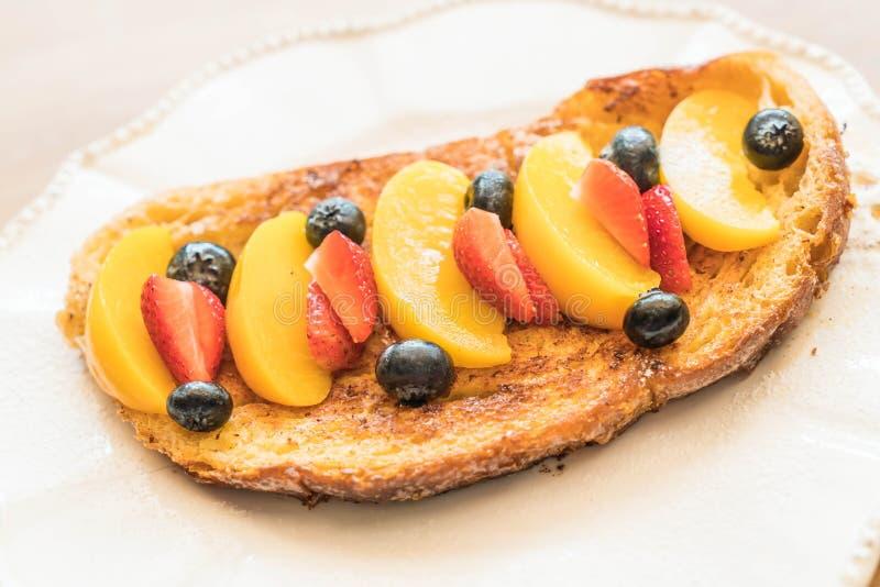 pane tostato francese con la pesca, la fragola ed i mirtilli immagini stock libere da diritti