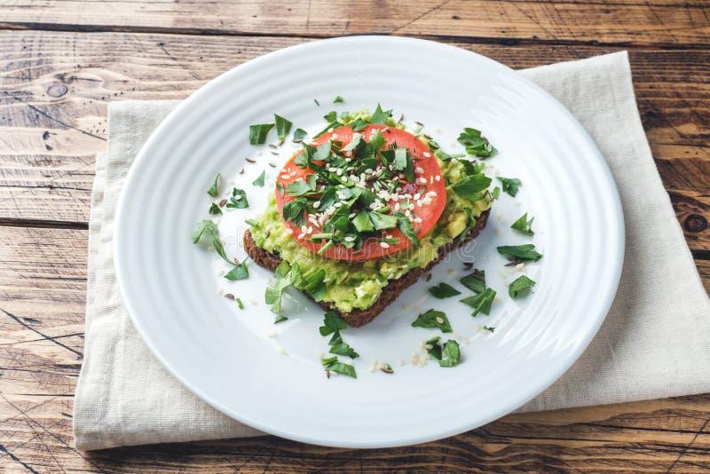 Pane tostato sano del pane tostato dell'avocado con la poltiglia ed i pomodori dell'avocado su un piatto fotografia stock