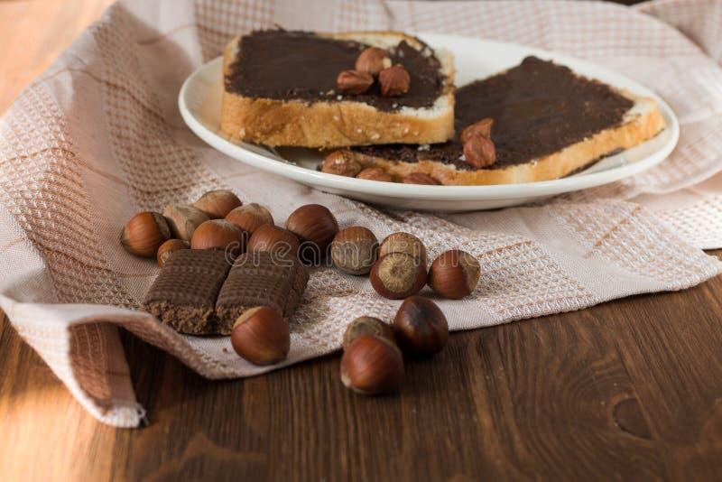 Pane tostato saporito con burro di arachidi su un piatto fotografia stock
