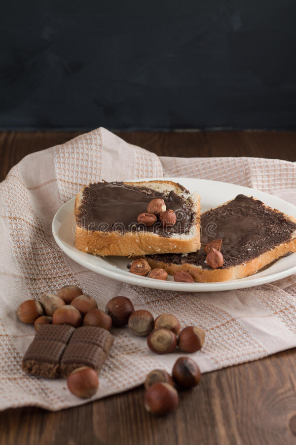 Pane tostato saporito con burro di arachidi su un piatto immagine stock libera da diritti