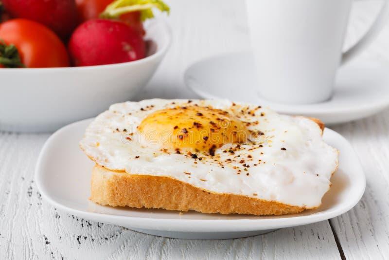 Pane tostato saporito del panino con l'avocado, il pomodoro e l'uovo affogato sul tagliere di legno fotografia stock libera da diritti