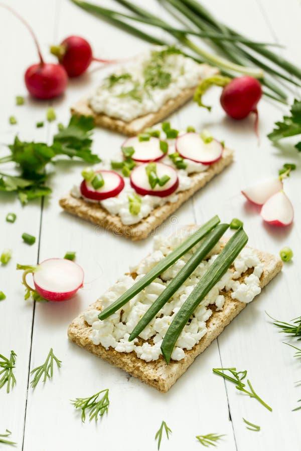 Pane tostato vegetariano con la ricotta, le erbe ed il ravanello su un fondo bianco Fuoco selettivo, foto verticale immagini stock