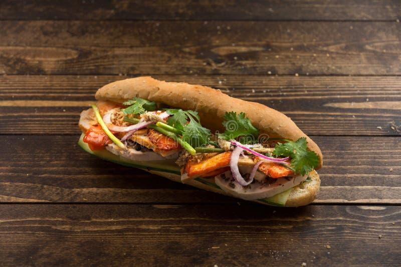 Pane vietnamita con carne di maiale e l'erba fritte sulla tavola di legno fotografia stock libera da diritti