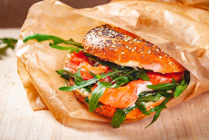Panecillo con la ensalada del queso cremoso, del salmón ahumado y del arugula en bolsa de papel marrón fotos de archivo