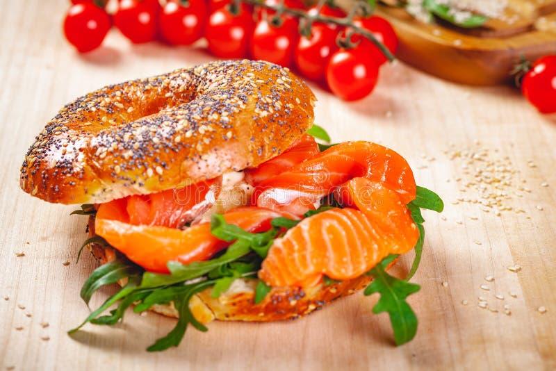 Panecillo con la ensalada del queso cremoso, del salmón ahumado y del arugula en el tablero de madera fotografía de archivo