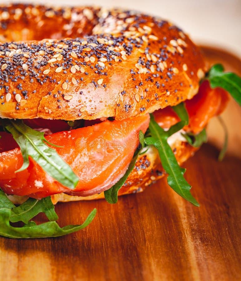 Panecillo con la ensalada del queso cremoso, del salmón ahumado y del arugula en el tablero de madera imagenes de archivo