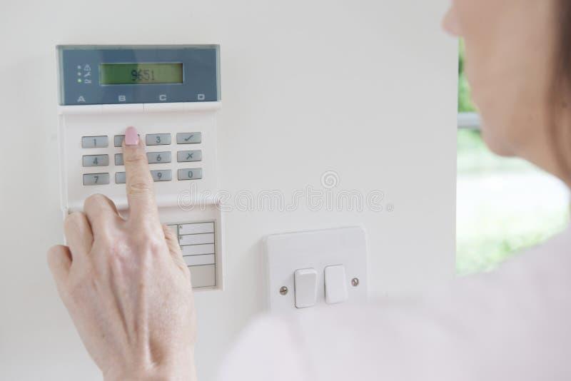 Panel de control del ajuste de la mujer en sistema de seguridad en el hogar fotografía de archivo