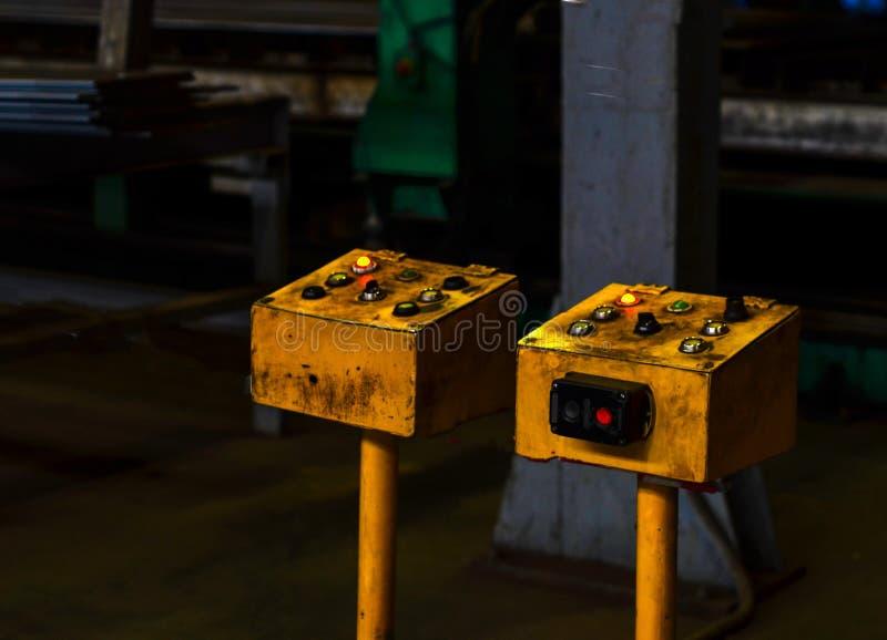 Panel de control eléctrico del viejo vintage amarillo con los botones para encender las máquinas en el taller para la producción  foto de archivo