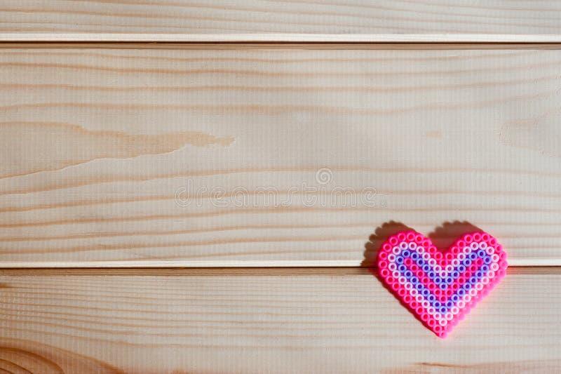 Panel lekkie drewniane deski i czerwony plastikowy serce zdjęcia stock