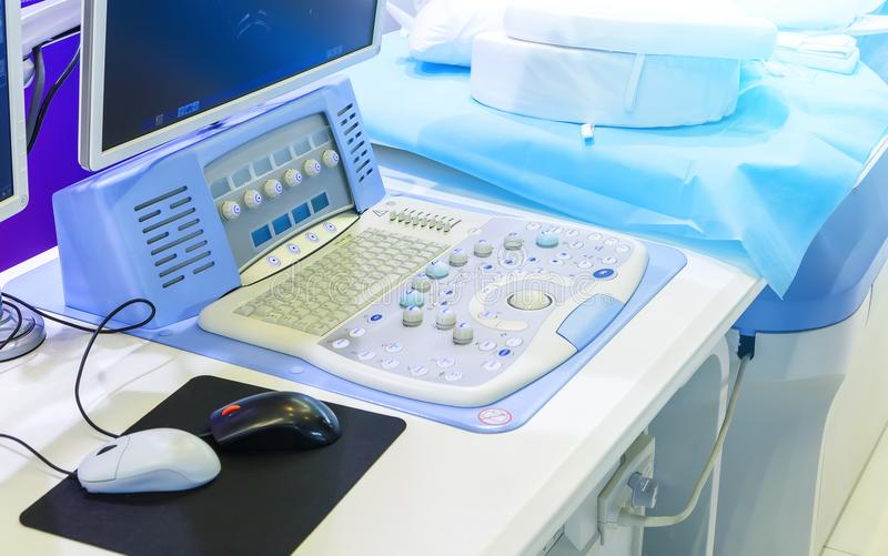 Panel with monitor equipment for ultrasound next to the couch and blue pillows. Medical ultrasound diagnostic machine readi to work royalty free stock image
