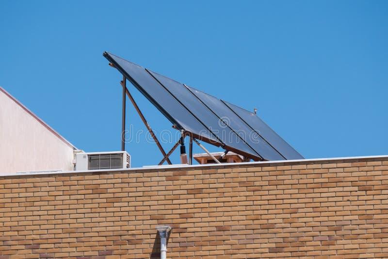 Panel słoneczny na dachu ceglany budynek mieszkaniowy z niebieskiego nieba tłem obrazy royalty free