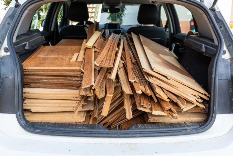 Paneles de madera cargados en la parte trasera de un coche blanco con guantes de mano de obra roja en primer plano imagenes de archivo