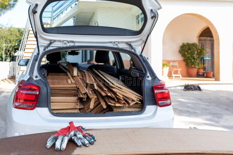 Paneles de madera cargados en la parte trasera de un coche blanco con guantes de mano de obra roja en primer plano foto de archivo