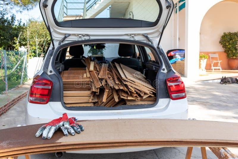 Paneles de madera cargados en la parte trasera de un coche blanco con guantes de mano de obra roja en primer plano fotografía de archivo