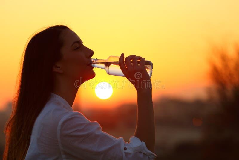 Panelljus av ett kvinnadricksvatten från en flaska fotografering för bildbyråer
