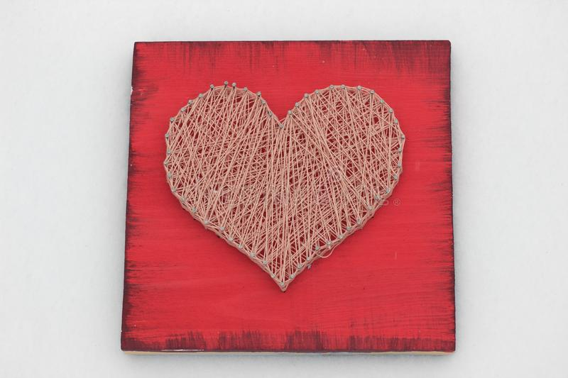 Panels of thread and nails, heart on a red background. string art. gift or decoration for February 14 and March 8. with love. Panels of thread and nails, heart stock image