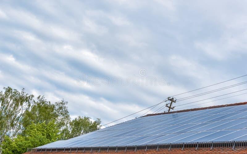 Panelu słonecznego system instalujący na dachu pod niebieskim niebem zdjęcie stock