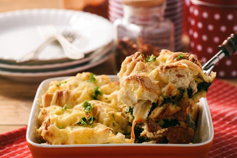 Panera eldfasta formen med höna, spenat, ägg och ost som är bekanta som skikt royaltyfri bild