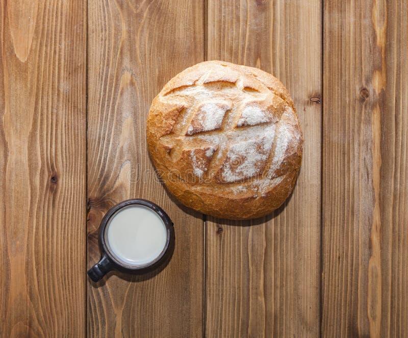 Panera och mjölka på en träbakgrund arkivbilder