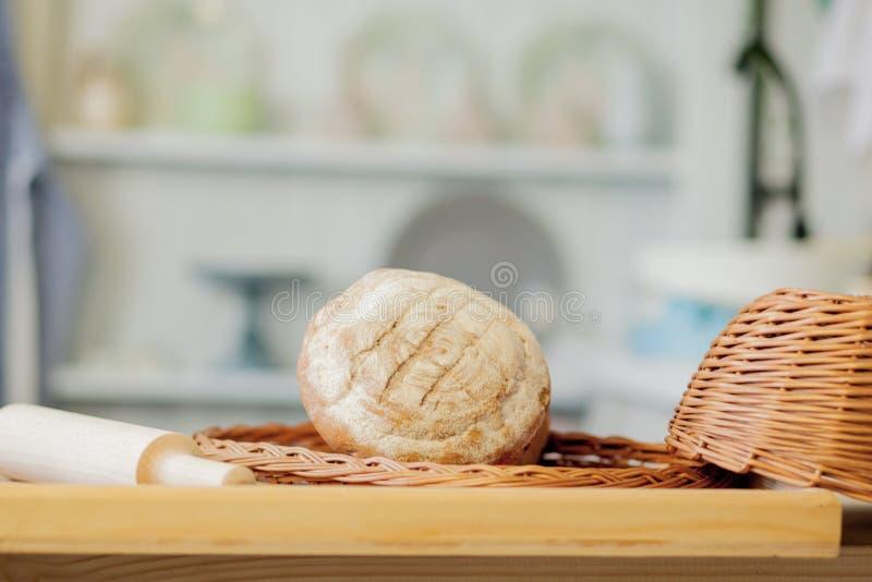 Panes cerca de una cesta de mimbre en una tabla en una cocina rústica Composición en cocina en el estudio de la foto foto de archivo libre de regalías