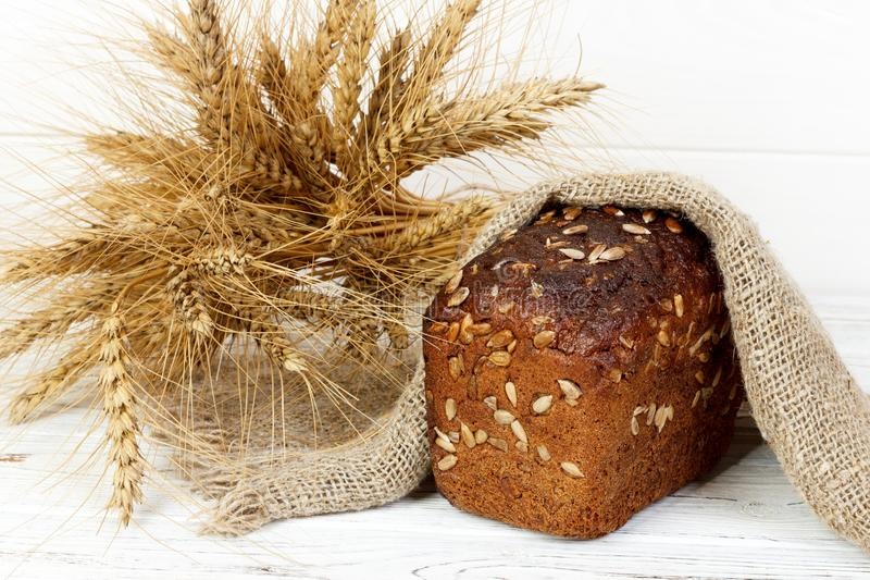 Panes de centeno rústicos hechos en casa con las semillas en un tablero de madera, cerca del trigo Foco selectivo, estilo rústico fotos de archivo libres de regalías