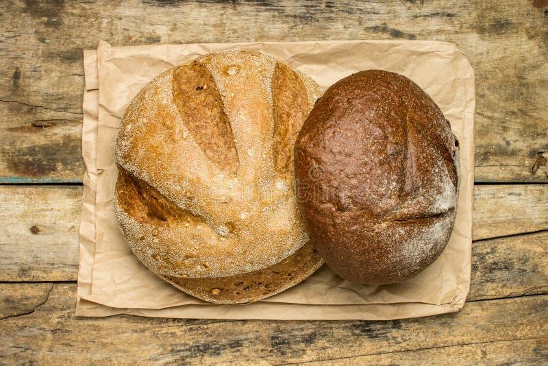 Panes de diversas especies de pan en el fondo de madera fotos de archivo