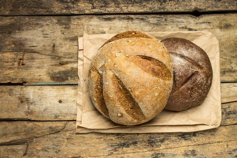 Panes de diversas especies de pan en el fondo de madera fotografía de archivo