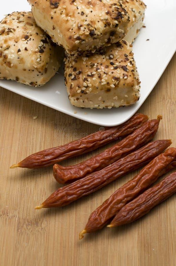 Panes de Foccacia con las salchichas en la tabla de cortar de madera imagenes de archivo