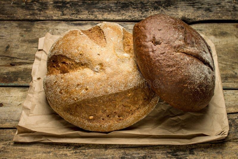 Panes del pan en bolsa de papel en el fondo de madera fotos de archivo