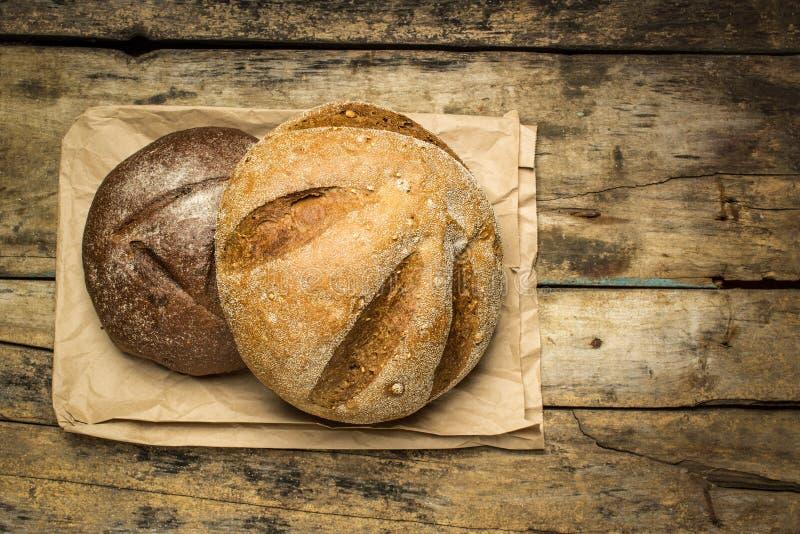 Panes del pan en la bolsa de papel que miente en el fondo de madera imagenes de archivo