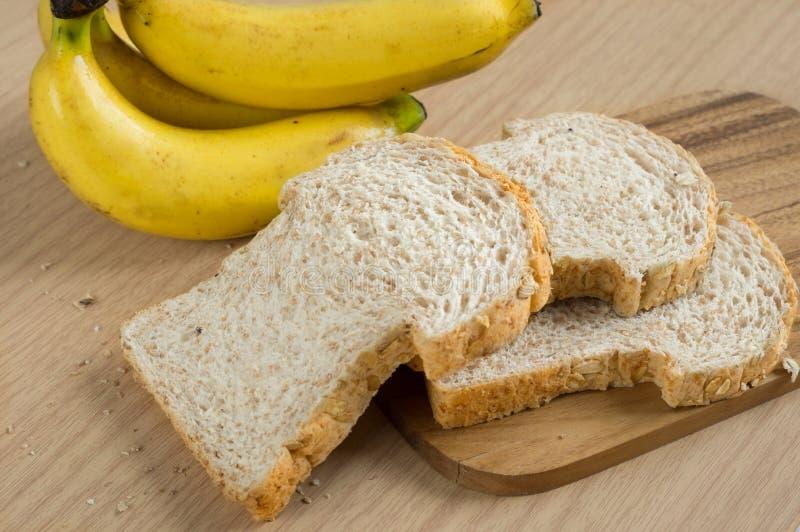 Panes del trigo integral con el plátano a bordo imagenes de archivo