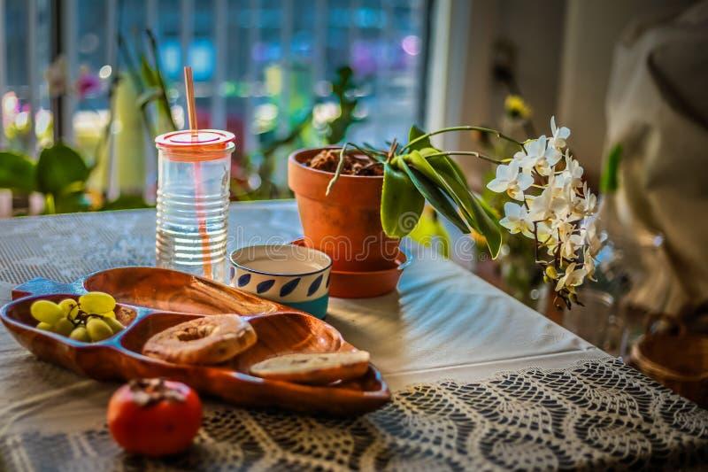 Panes en la tabla con las frutas, la bebida y un pote de flores foto de archivo