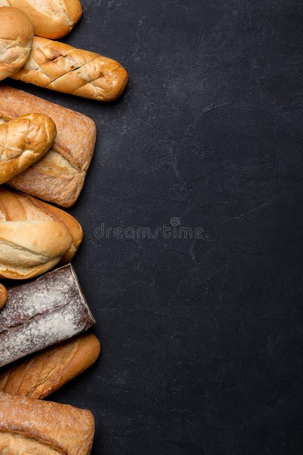Panes frescos en la tabla oscura foto de archivo