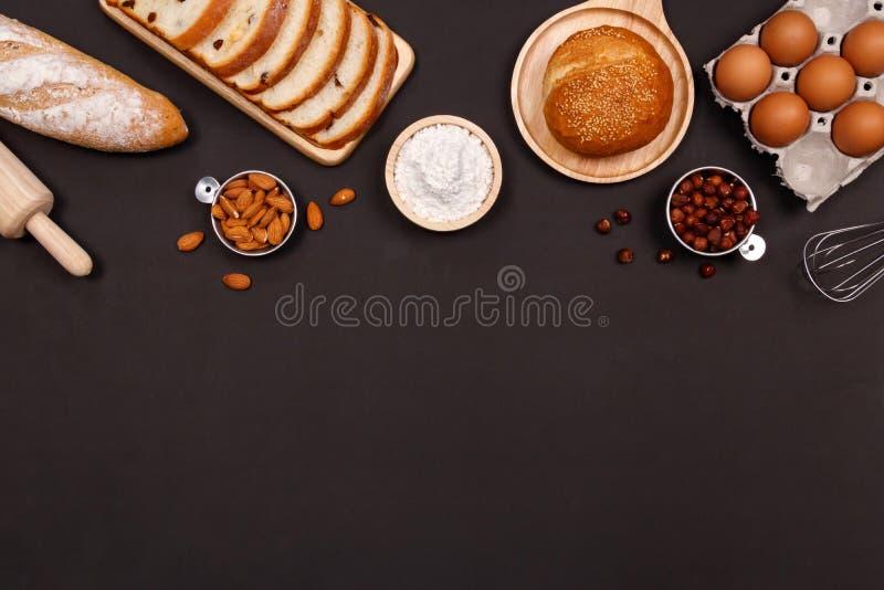 Panes hechos en casa o ingredientes del bollo, del cruasán y de la panadería, harina, nueces de la almendra, avellanas, huevos en imagenes de archivo
