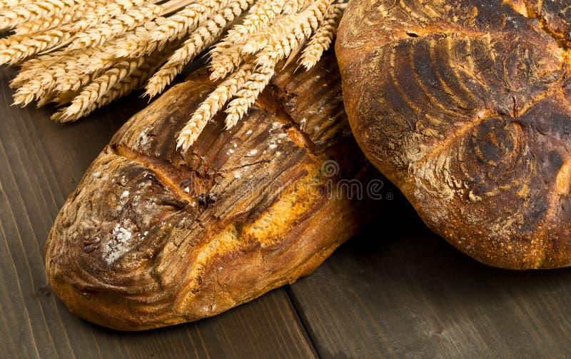 Panes hechos a mano del pan con los oídos del trigo foto de archivo