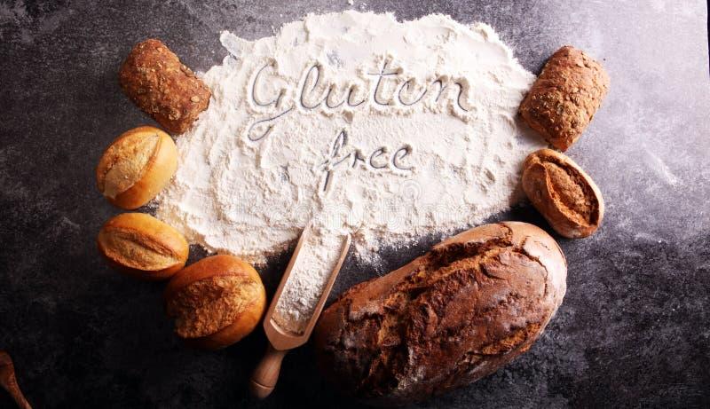 panes libres del gluten, palabra del glutenfree escrita y rollos de pan en g foto de archivo libre de regalías