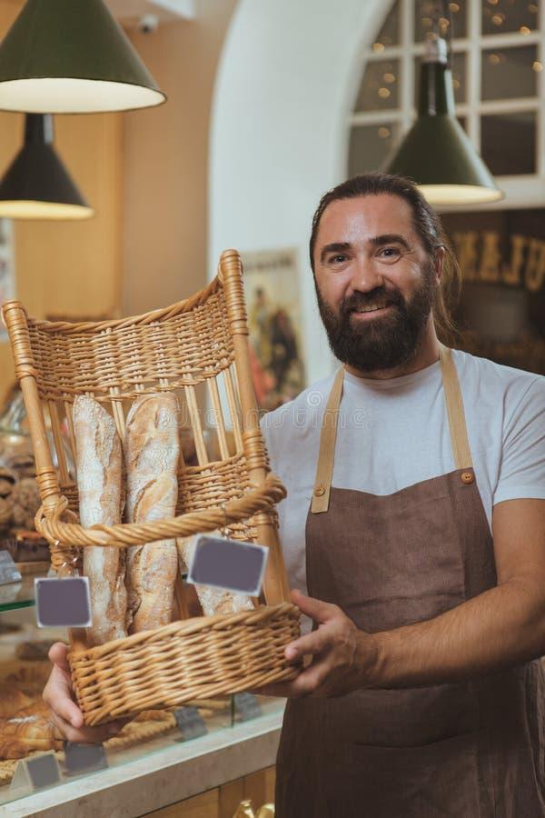 Panettiere barbuto allegro che gode del lavoro al suo deposito immagini stock libere da diritti