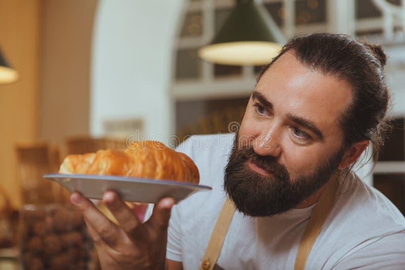 Panettiere barbuto allegro che gode del lavoro al suo deposito fotografie stock