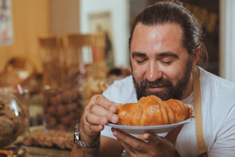 Panettiere barbuto allegro che gode del lavoro al suo deposito fotografie stock libere da diritti