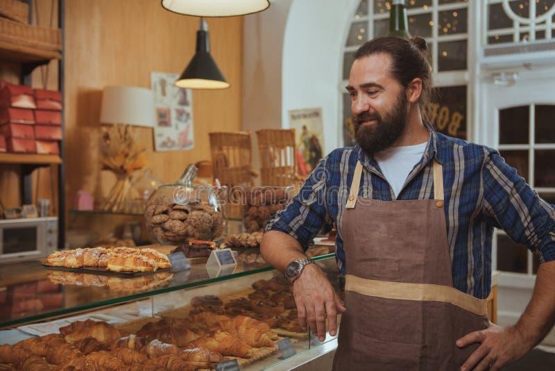 Panettiere barbuto allegro che gode del lavoro al suo deposito fotografia stock