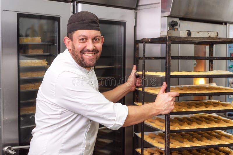 Panettiere che mette uno scaffale delle pasticcerie nel forno in forno o nel negozio di pasticceria immagine stock libera da diritti