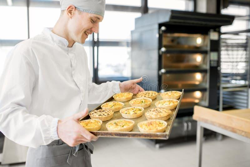 Panettiere con i panini alla fabbricazione fotografia stock