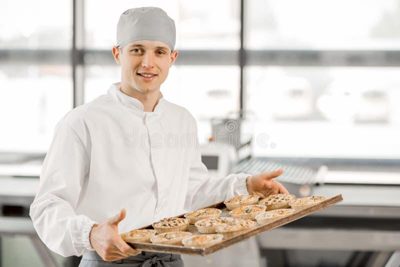 Panettiere con i panini alla fabbricazione immagine stock libera da diritti