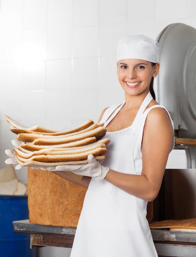 Panettiere femminile Carrying Bread Waste in forno fotografie stock
