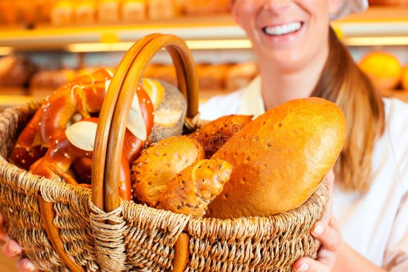 Panettiere femminile che vende pane dal cestino in forno immagini stock libere da diritti