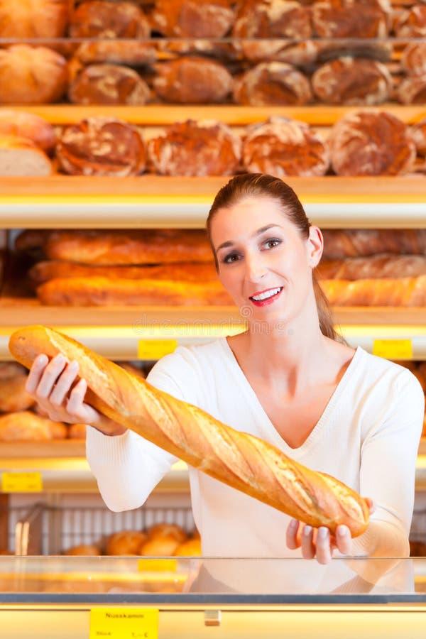Panettiere femminile nel suo forno con il baguette immagine stock