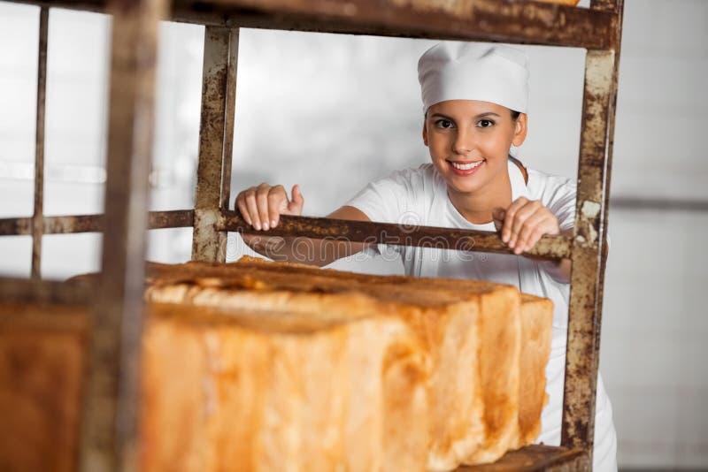 Panettiere femminile sicuro Pulling Bread Rack fotografia stock libera da diritti