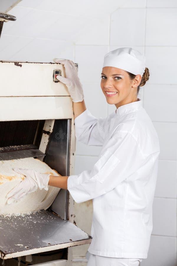 Panettiere femminile sicuro Using Bread Slicer a fotografie stock