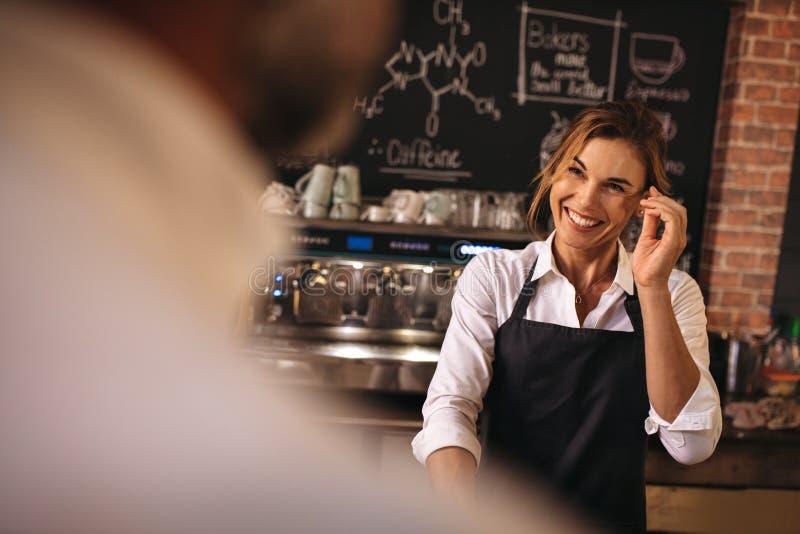 Panettiere femminile sorridente che lavora in un forno fotografie stock libere da diritti
